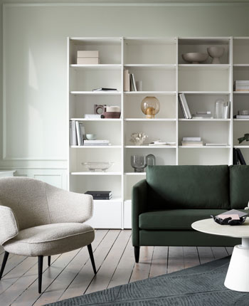 White wall system,  green sofa, armchair and coffee table