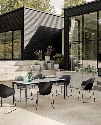 Black outdoor dining chairs and outdoor dining table with grey ceramic glass tabletop.