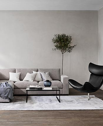 Grey corner sofa and black leather armchair