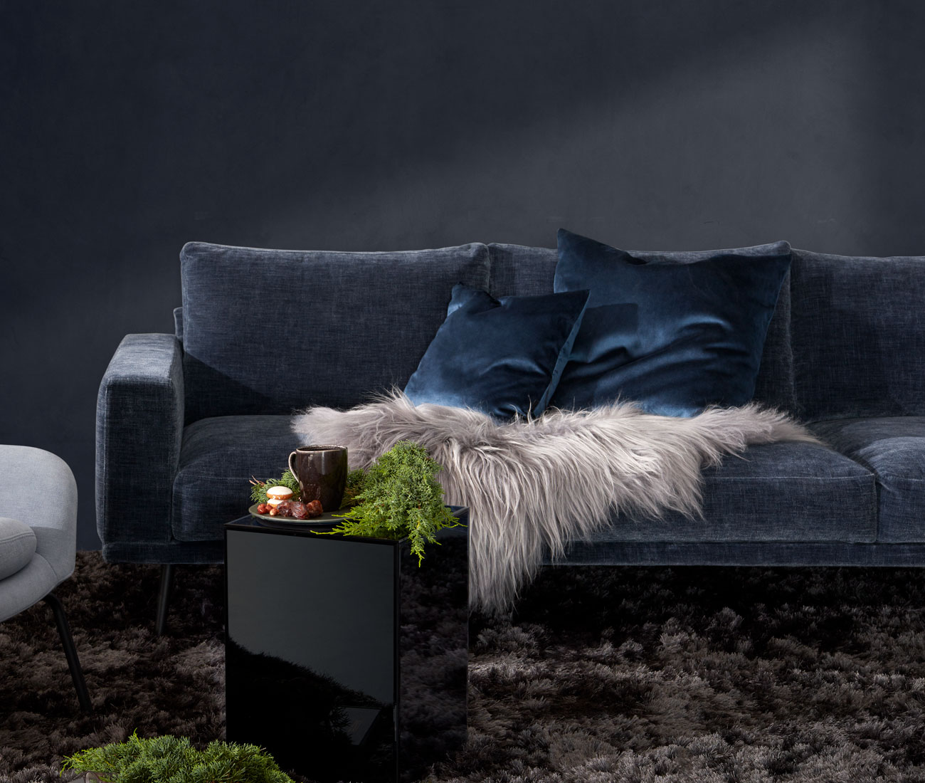 Dark blue velvet Sofa with blue velvet cushions and block mirror table