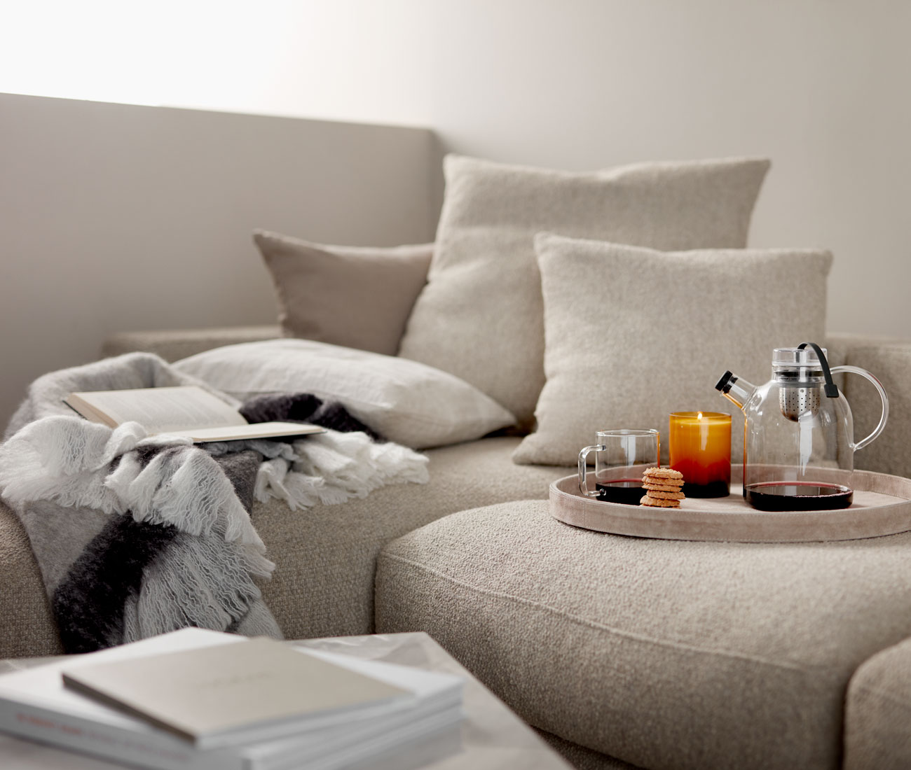 Beige sofa and cushions with light wooden tray with tea