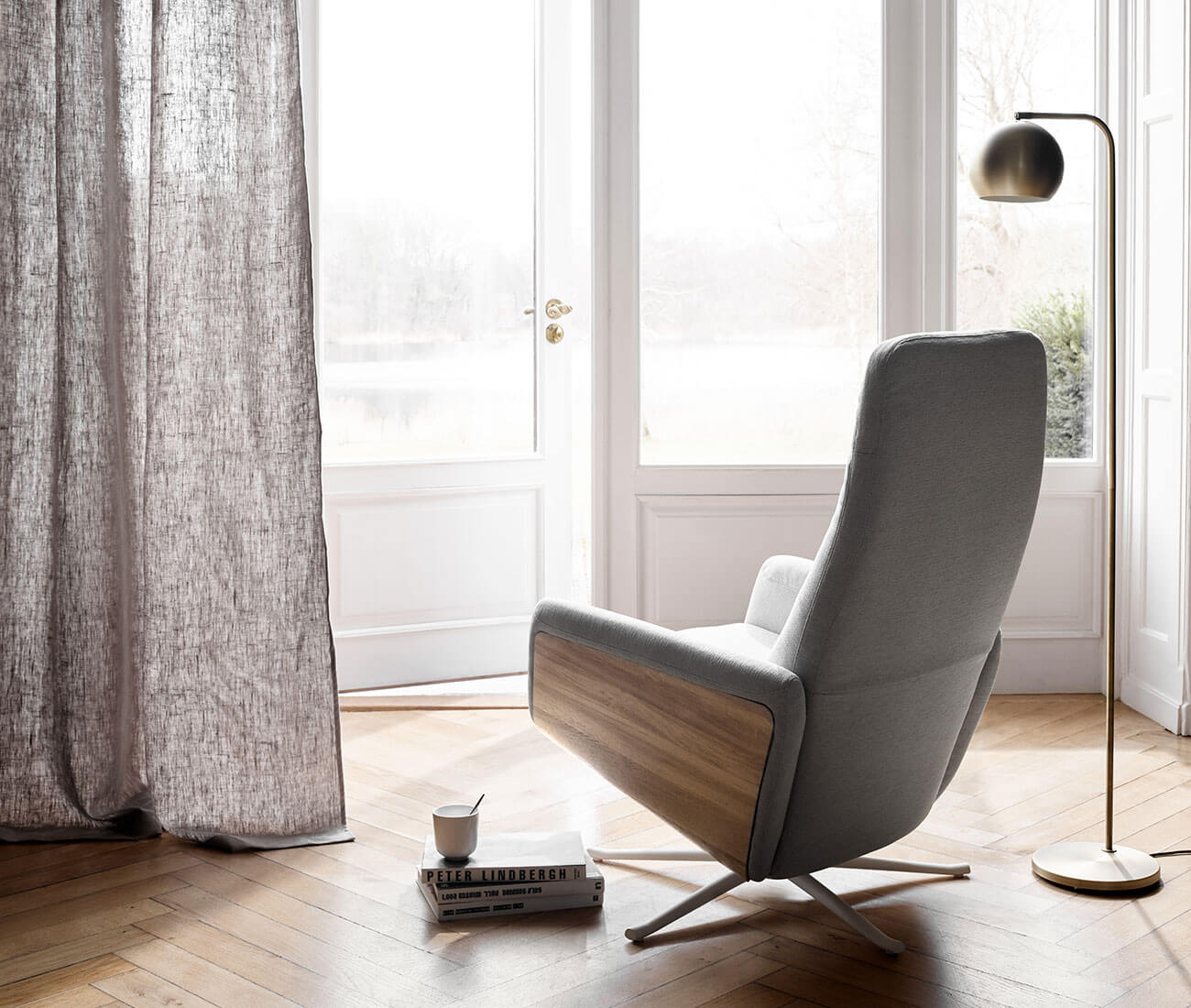 Recliner with swivel function in beige fabric. Brass coloured floor lamp.