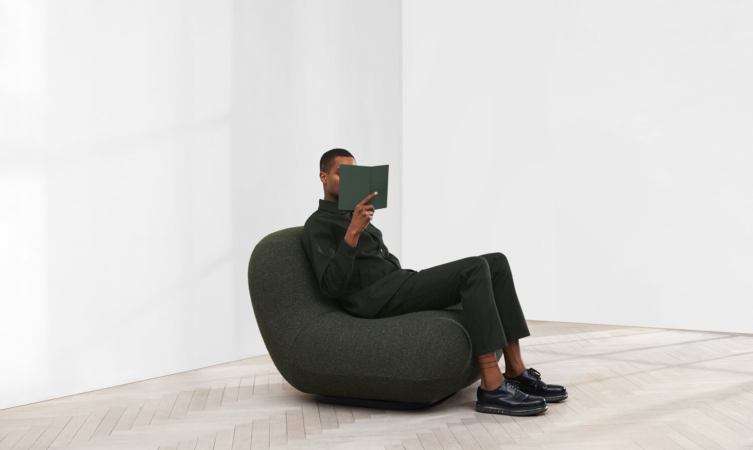 Man holding up a book, while sitting in the Chelsea chair