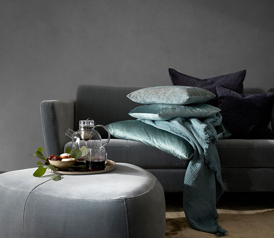 Dusty green velvet sofa with cushions in different blue tones and a grey footstool