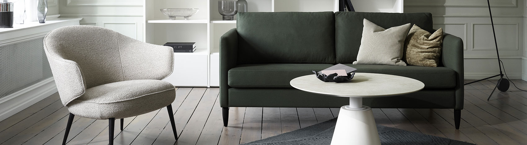Indivi sofa in a dark green fabric, light grey Charlotte chair and a light marble Madrid coffee table