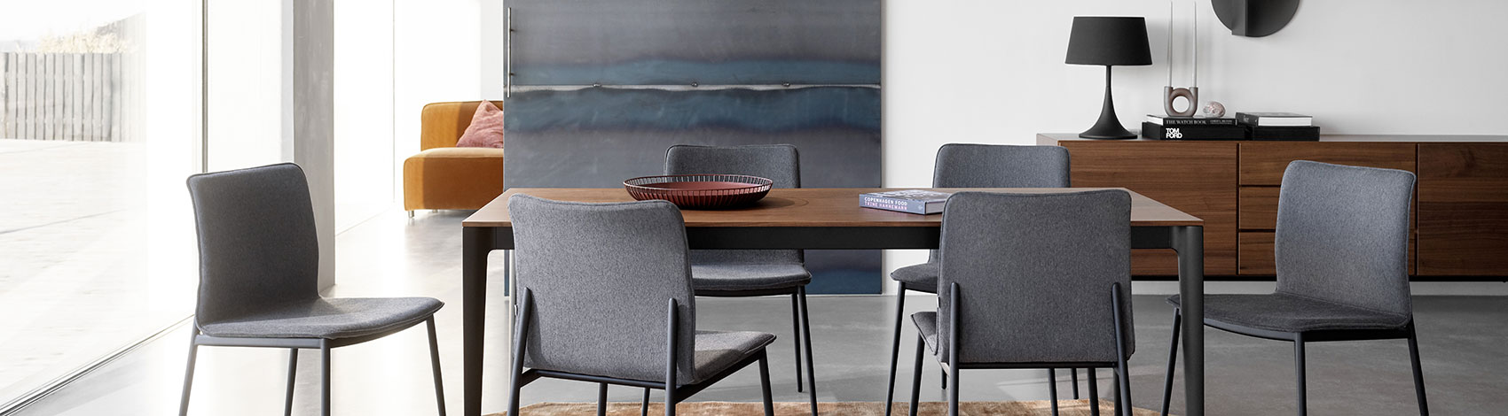 Wooden table and grey fabric dining chairs