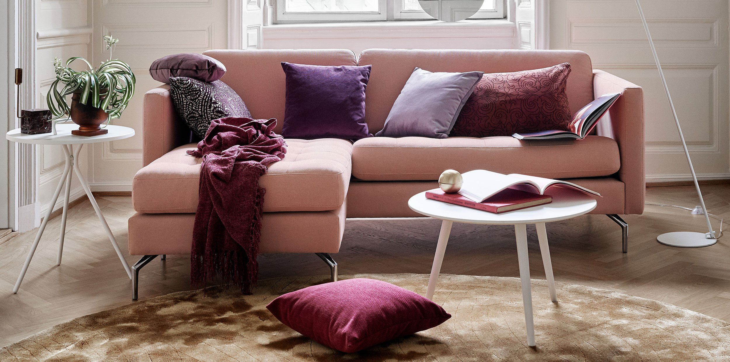 Osaka sofa in dusty red with different shades of purple cushions and white coffee table