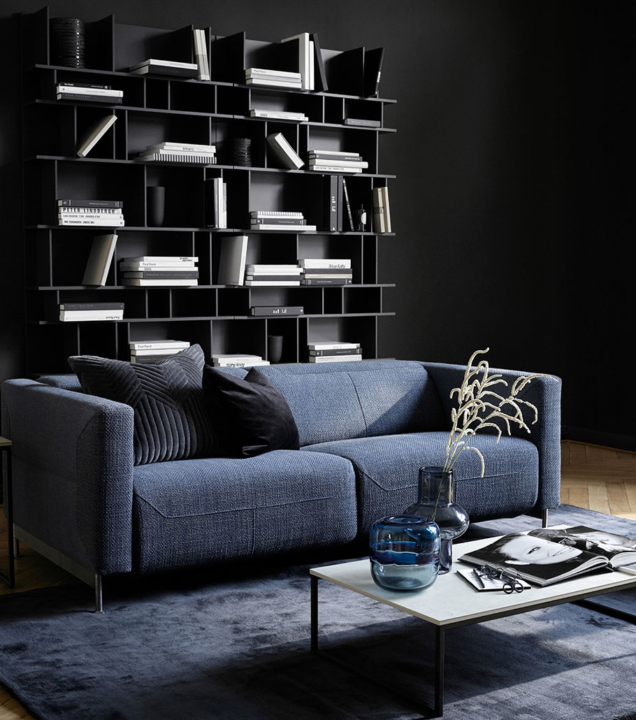 Dusty blue Parma sofa with grey and black cushions and black Copenhagen wall system