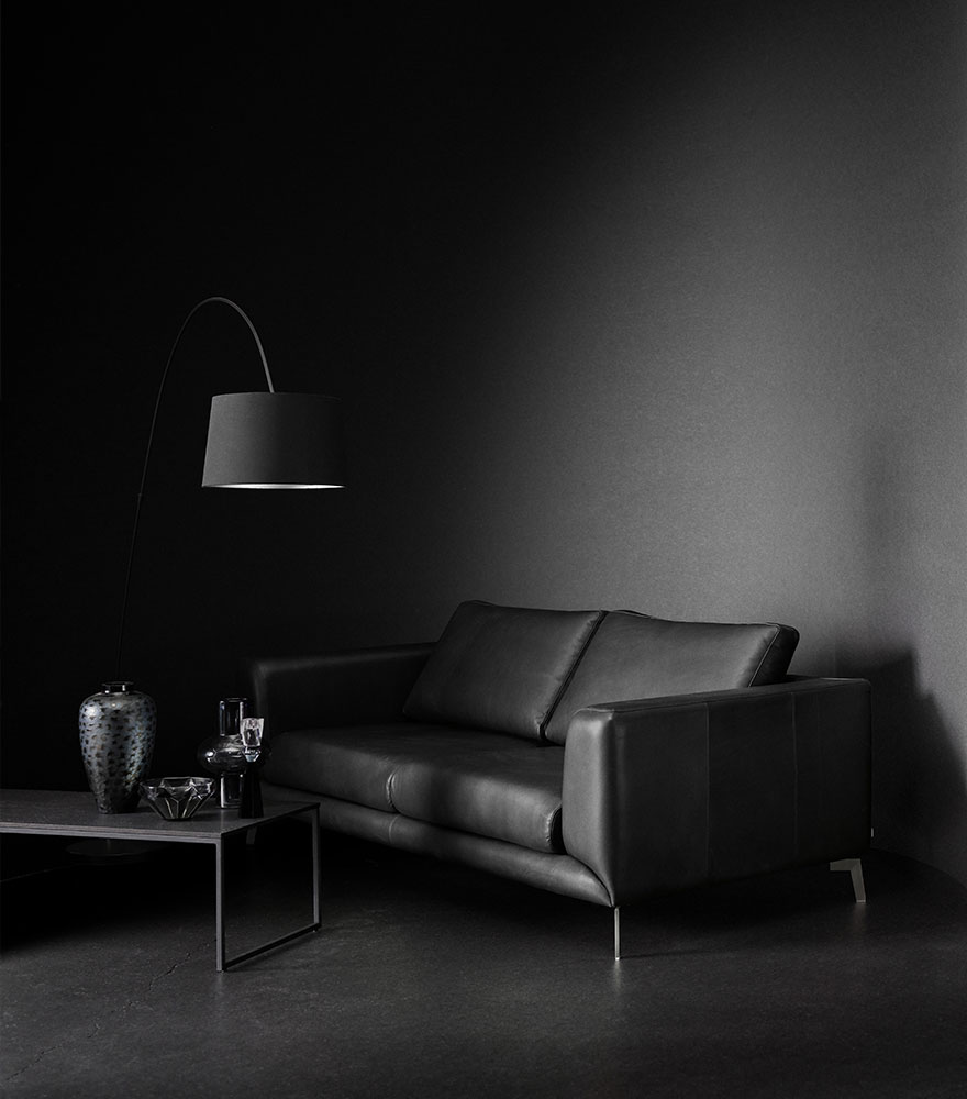 Black leather sofa with black coffee table and black floor lamp