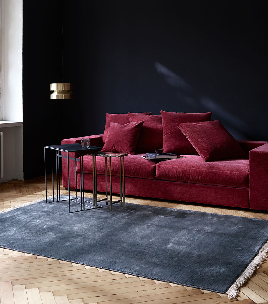 Living room with red sofa and dark grey rug