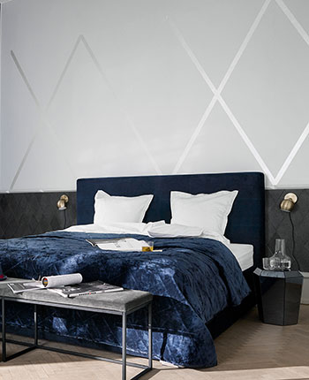 Bed with dark headboard and blue bedspread and a bench with grey seat