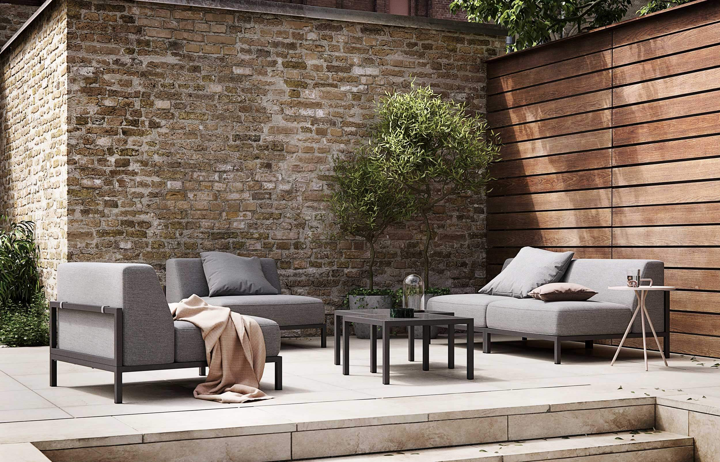 BoConcept's Rome garden sofa system in walled terrace garden with plants and trees