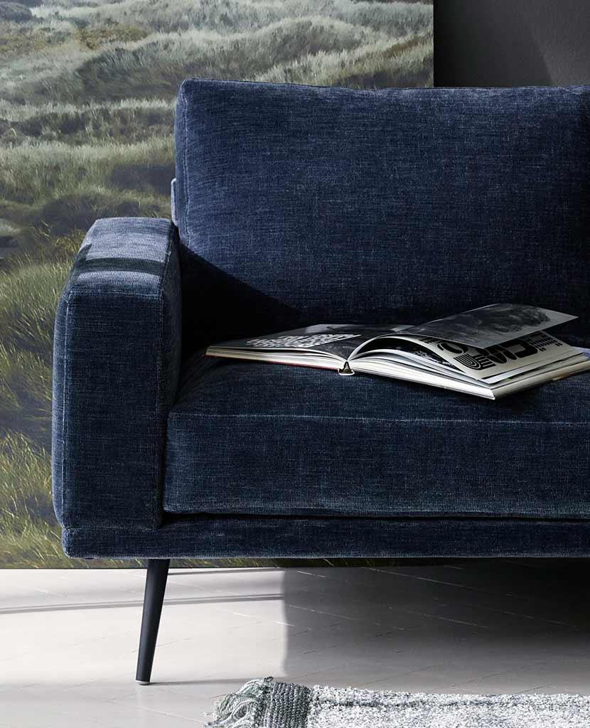 Coastal blue sofa with a catalogue on it