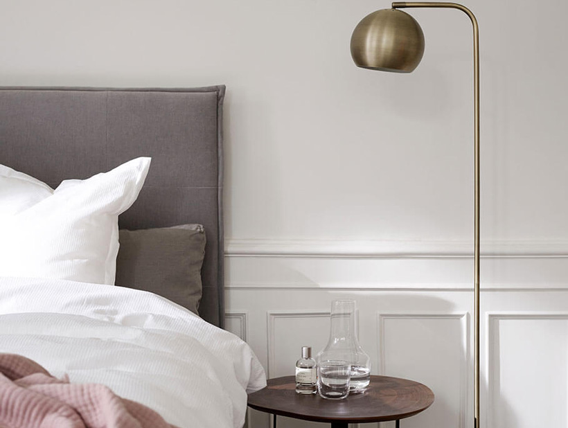 Bed with grey upholstered headboard with walnut side table and antique brass coloured floor lamp.