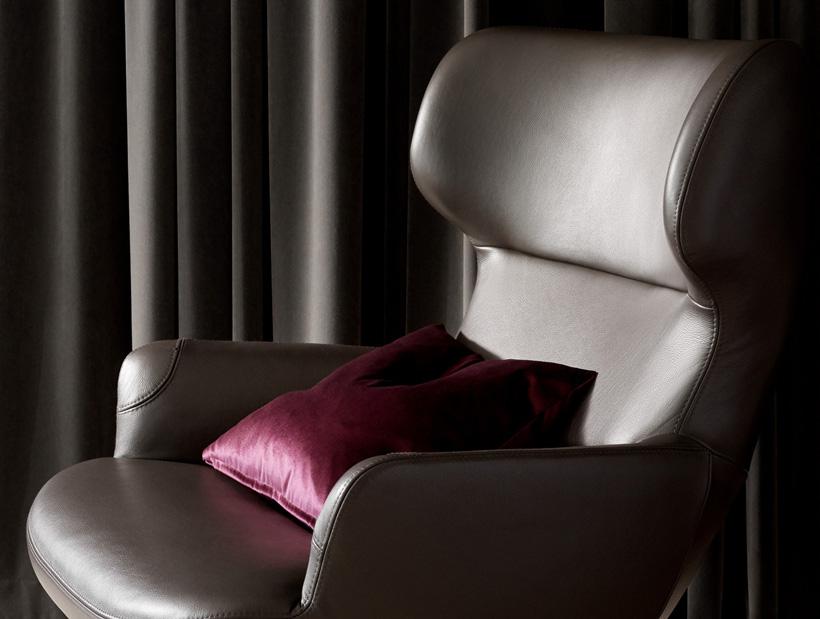 Dark brown leather chair with purple cushion