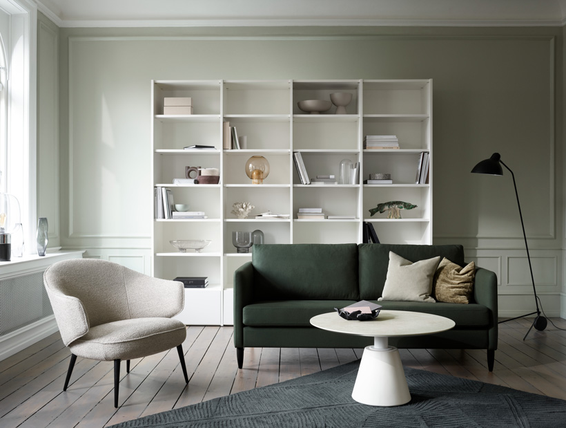 White Copenhagen wall system and dark green Indivi sofa, a light grey Charlotte chair and a white Madrid coffee table