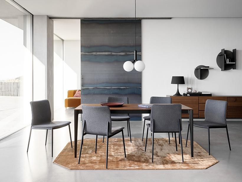 Stůl Torino s dýhou v barvě ořechu a černými nohami a jídelní židle Newport s tmavě šedým čalouněním a černými nohami