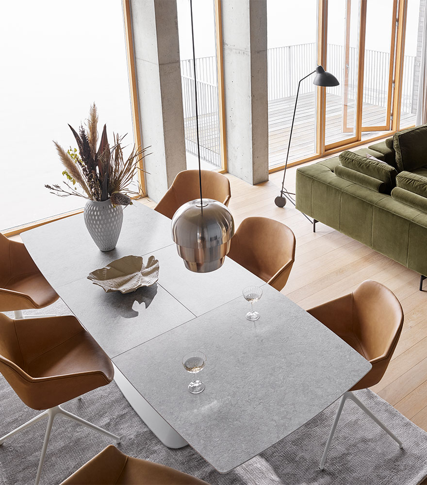 Light gray dining table with camel leather chairs