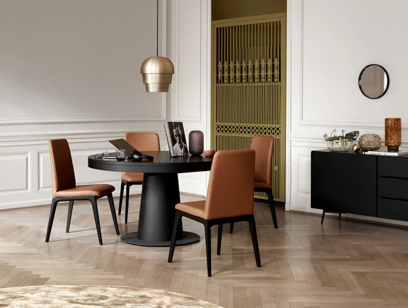 Black round dining table and brown leather dining chairs