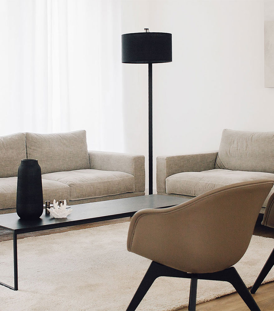 White sofa, black coffee table and brown Adelaide chair
