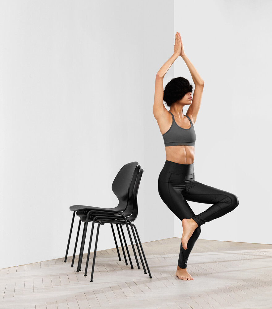 Woman doing yoga next to a stack of Florence chairs