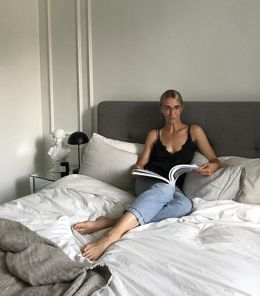kvinne som leser et blad i sengen