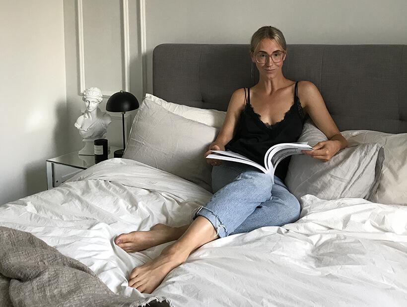 kvinde i seng, der læser i et magasin