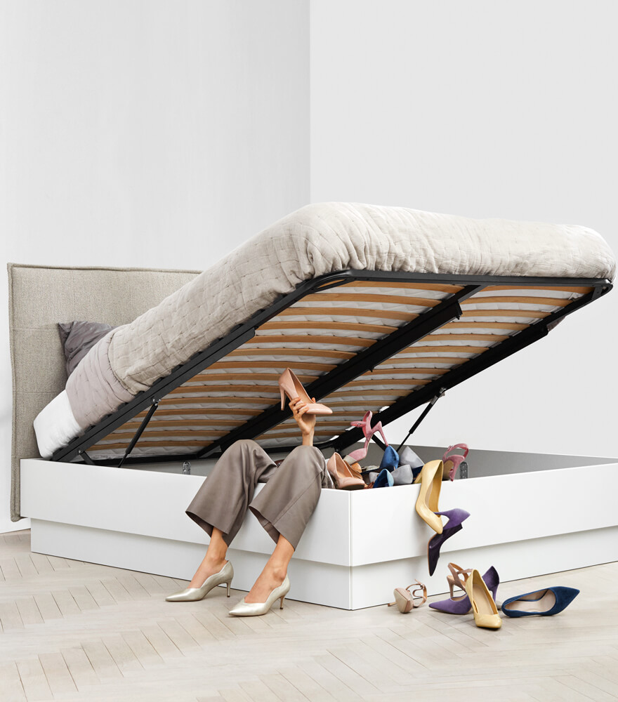 Woman lying in Lugano storage bed under a lot of shoes