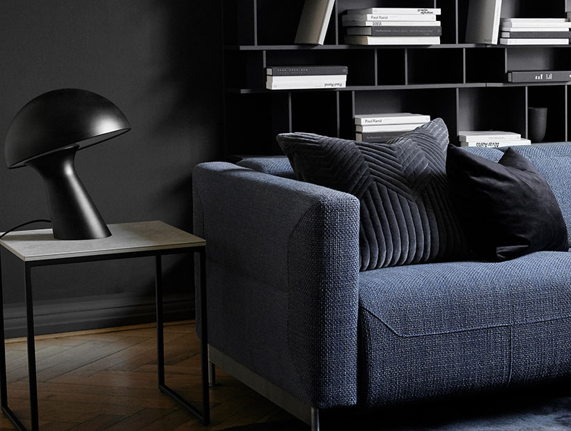 Blue sofa on living room next to small table with a lamp on it
