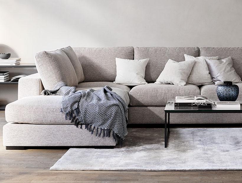 Light grey corner Sofa with Cushions on it