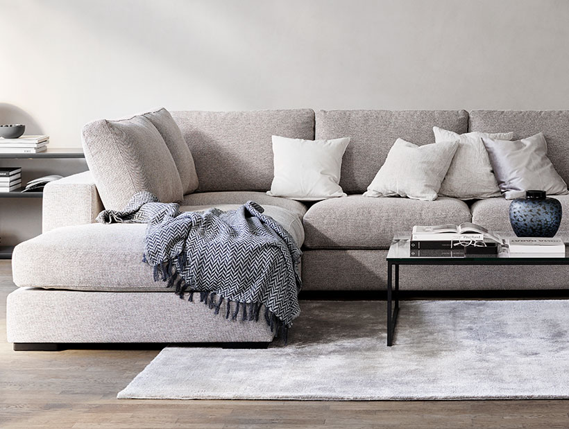 Light grey corner Sofa with Cushions on it