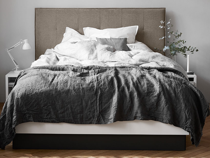 Brown Bed with cushions on it and side tables next to it